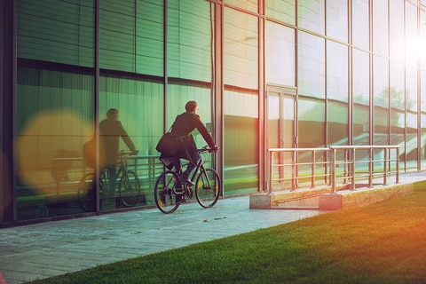 Rear view of a handsome man, on the way to work, riding bicycle beside the modern office building. The man is casually dressed and wears eyeglasses and carries black briefcase hung on shoulder. Blurred motion, copy space has been left.